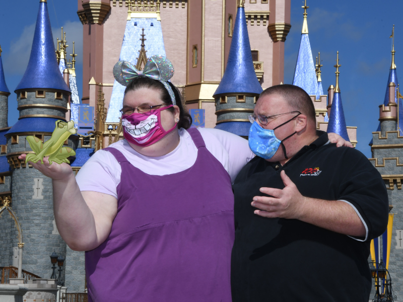 April holding animated frog with husband in front of Cinderella Castle