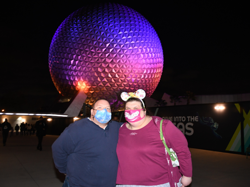 Nighttime picture of April and husband in front of Spaceship Earth
