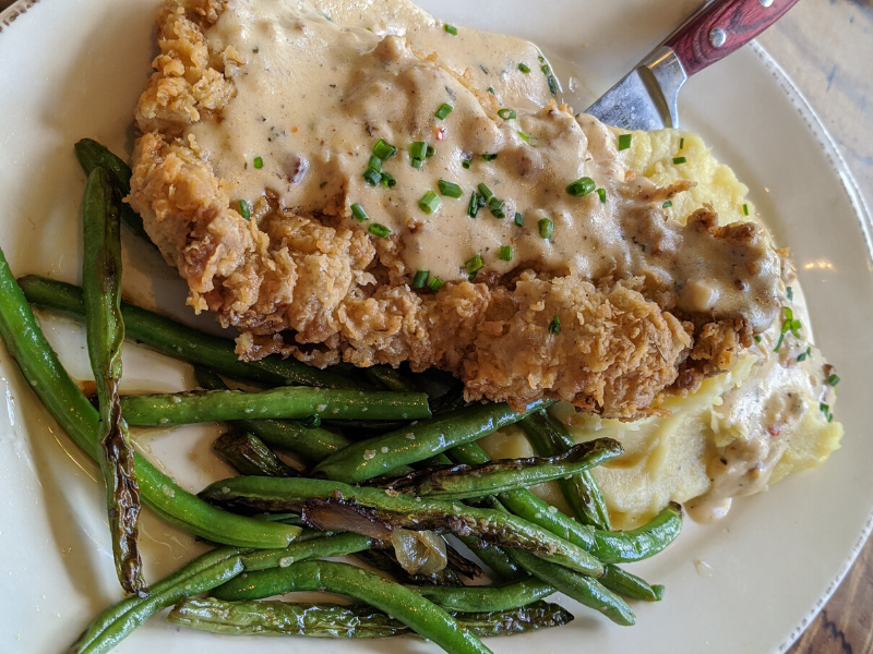 Country fried steak with masked potatoes and green beans on white plate