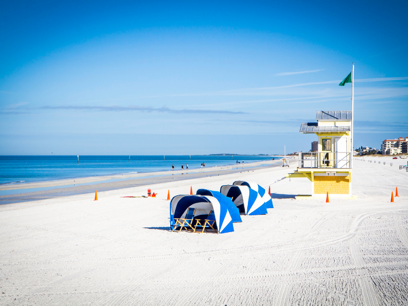 white sand Clearwater Beach with life guard shack and chairs with covers
